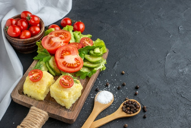 Vista ravvicinata di pomodori freschi tagliati e cetrioli formaggio su tavola di legno posate spezie in cucchiai su superficie nera