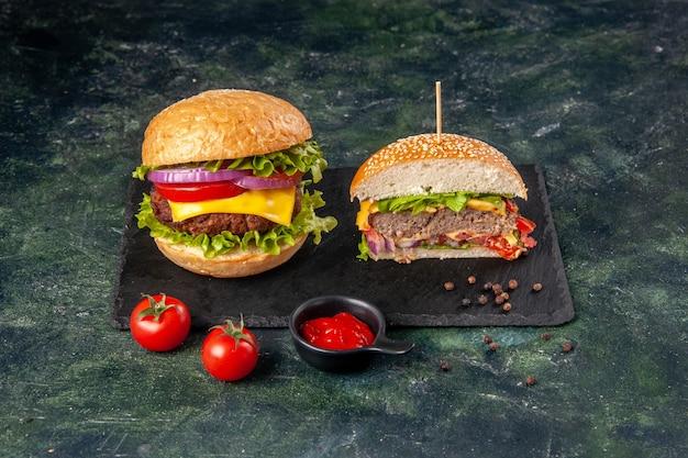 Vista ravvicinata di interi gustosi panini e pomodori tagliati con gambo su vassoio nero su superficie di colore misto scuro