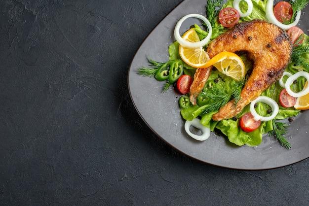 Vista ravvicinata di deliziose farine di pesce e verdure servite con verde su un piatto di colore scuro su superficie nera con spazio libero