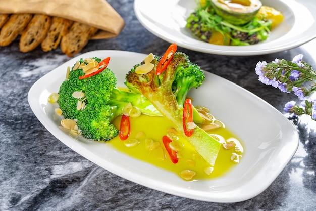 Chiuda sulla vista sui broccoli fritti deliziosi con il peperoncino rosso e il burro serviti sul piatto bianco sulla tavola di marmo