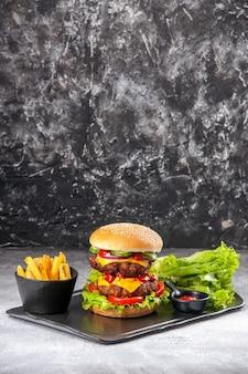 Vista ravvicinata di deliziosi panini fatti in casa e patatine fritte di ketchup con forchetta verde su vassoio nero su superficie isolata grigia in difficoltà