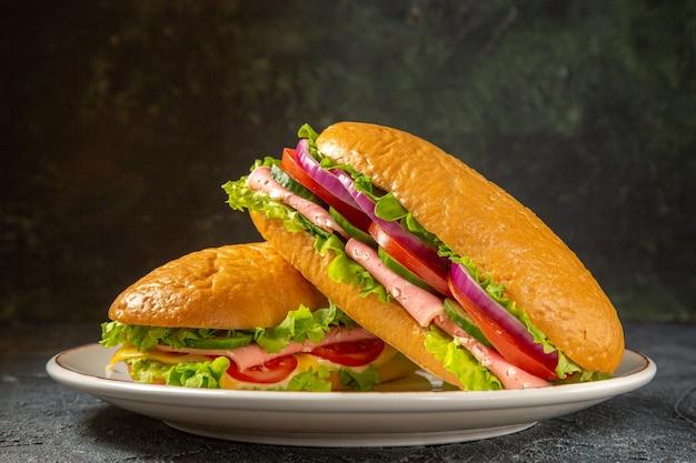Vista ravvicinata di deliziosi panini fatti in casa su un piatto bianco su superficie nera in difficoltà con spazio libero free