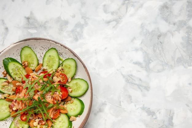 Vista ravvicinata di una deliziosa insalata decorata con cetriolo tritato e verdure su una superficie bianca macchiata con spazio libero