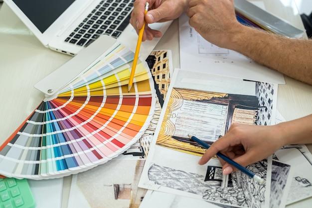 Vista ravvicinata sul posto di lavoro del designer che parla di un nuovo progetto