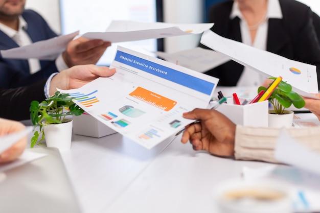 Vista ravvicinata della scrivania piena di statistiche cartacee mostrate su grafici e diversi uomini d'affari
