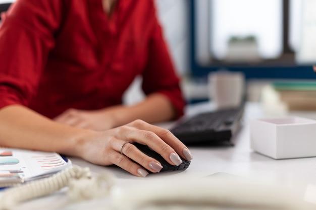 Primo piano visualizza i dettagli delle mani della donna d'affari nell'ufficio aziendale