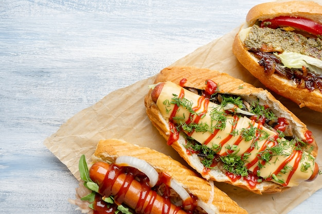 Chiuda sulla vista su diversi hot dog in stile alimentare con guarnizioni su superficie di legno leggera