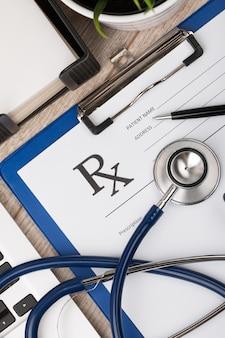 Vista ravvicinata del tavolo da lavoro medico. stetoscopio, laptop e modulo di prescrizione vuoto. vista dall'alto
