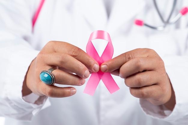 Chiuda sulla vista delle mani di medico femminile che tengono nastro rosa del cancro al seno.