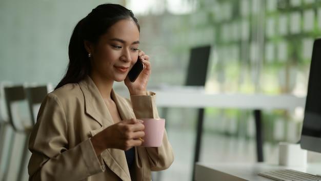 Vista ravvicinata dell'imprenditore femminile che parla al telefono mentre fai una pausa caffè nella stanza dell'ufficio