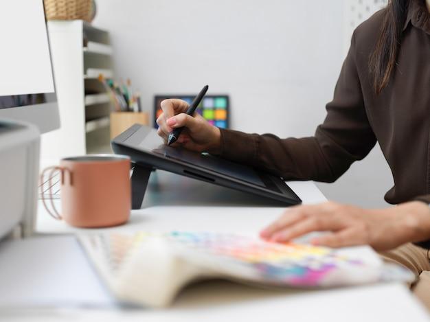 Vista ravvicinata delle mani femminili di designer grafico che lavorano con tavoletta grafica e campione di colore