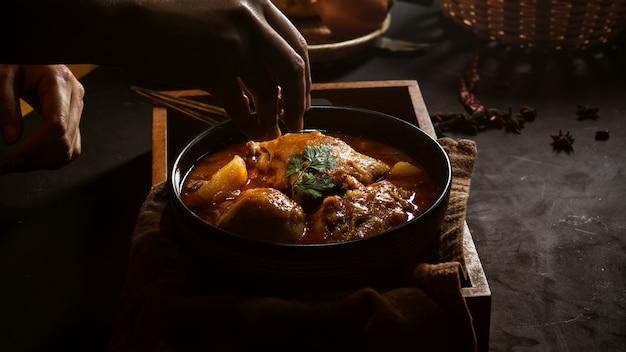 Vista ravvicinata della mano femminile che cucina il pollo massaman curry per servire nel ristorante tailandese