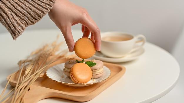 Vista ravvicinata della femmina di raccolta a mano macaron francese da un piatto sul tavolino da caffè con tae cup