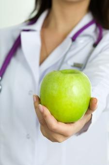 Vista ravvicinata della mano di medico femminile che offre mela verde. cibo sano e stile di vita, assistenza sanitaria, servizio medico e concetto di dieta alimentare