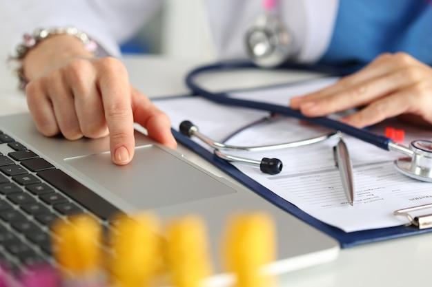 Vista ravvicinata della medicina femminile medico o studente mani che lavorano al computer portatile