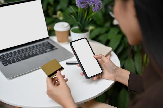Vista ravvicinata dello shopping online femminile su smartphone e pagamento con carta di credito