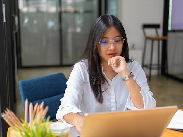 Vista ravvicinata della lavoratrice concentrandosi sul suo lavoro con laptop e forniture in ufficio