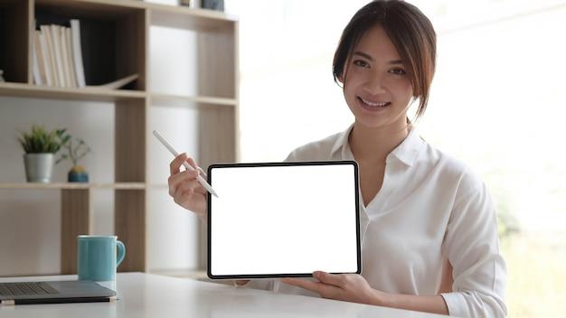 Vista ravvicinata della lavoratrice che mostra lo schermo del tablet mentre si sta in piedi nella stanza dell'ufficio.