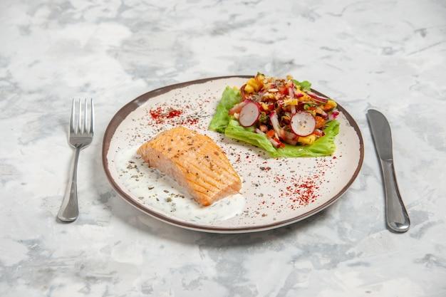 Vista ravvicinata di farina di pesce e deliziosa insalata su un piatto e posate su una superficie bianca macchiata con spazio libero free