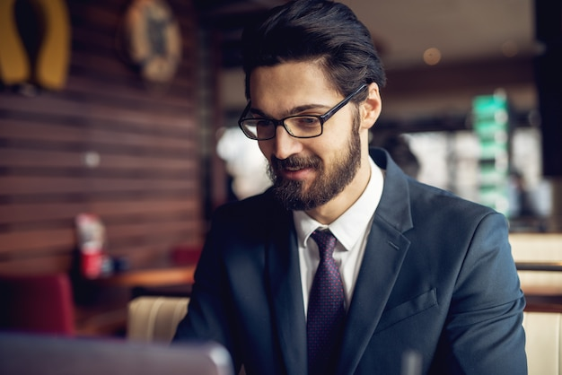 Chiuda sulla vista di giovane uomo d'affari barbuto riuscito professionale concentrato in vestito che lavora ad un caffè.