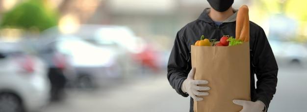 Chiuda sul punto di vista dell'uomo di servizio di distribuzione di alimenti che tiene la borsa dell'alimento fresco