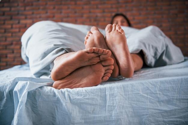 Vista ravvicinata dei piedi di una coppia che dorme insieme in camera da letto al mattino.