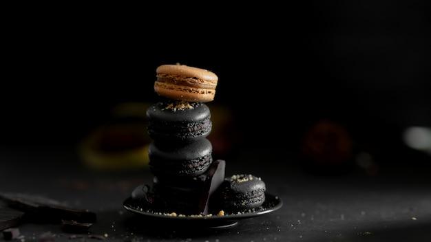 Chiuda sulla vista dei macarons francesi di colore scuro sulla banda nera