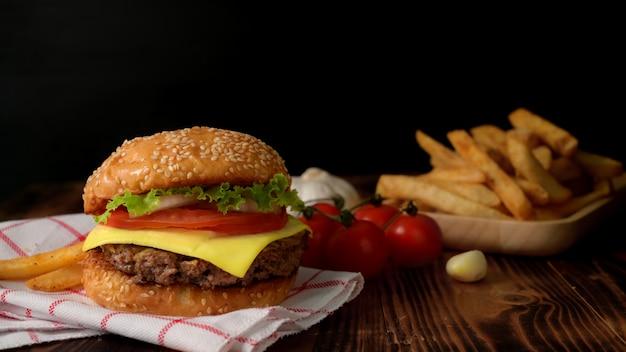 Chiuda sulla vista dell'hamburger di manzo saporito fresco con le patate fritte e gli ingredienti