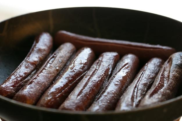 Vista ravvicinata di salsicce fritte. carne di pesce. cucinare il cibo. foto di alta qualità