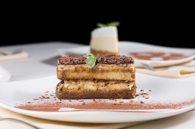 Vista ravvicinata della fetta gourmet di deliziosa torta al cioccolato su piastra bianca con polvere di cioccolato. servito sul tavolo per l'ospite.