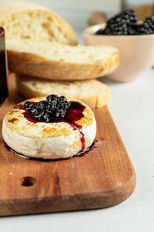 Chiuda sulla vista su camembert grigliato con marmellata di more, noci e chiabatta su sfondo grigio. copia spazio. formaggio. cibo gustoso a pranzo. focalizzazione morbida. cibo per il vino
