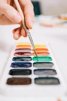 Vista ravvicinata della mano che tiene un pennello e mescola i colori delle vernici sulla tavolozza. concetto di educazione artistica, corso d'arte o studio e terapia artistica. tavolozza dei colori delle vernici. vernice colorata.