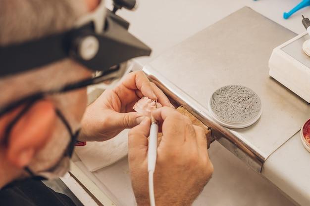 Vista ravvicinata delle mani di un uomo adulto che modella uno stampo dentale con cera utilizzando un file elettrico in un laboratorio odontotecnico specializzato in ceramica ossea dentale per creare corone di porcellana.