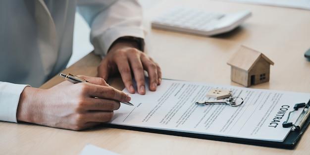 Vista ravvicinata delle mani di una donna d'affari che firma i documenti della casa di leasing e ha le chiavi dell'appartamento su scartoffie.