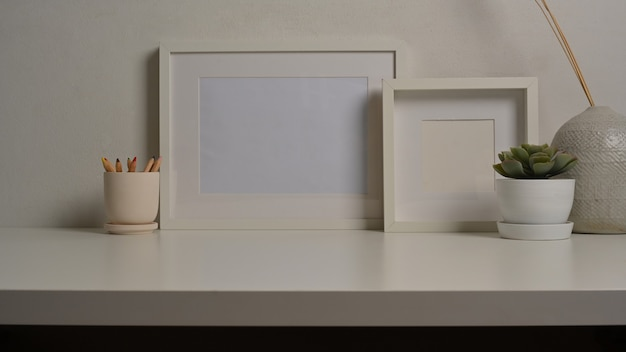 Vista ravvicinata di interior design per la casa con mock up frame vaso e vaso sulla scrivania bianca