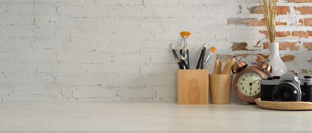 Vista ravvicinata della scrivania da casa con fotocamera, cancelleria, decorazioni e copia spazio