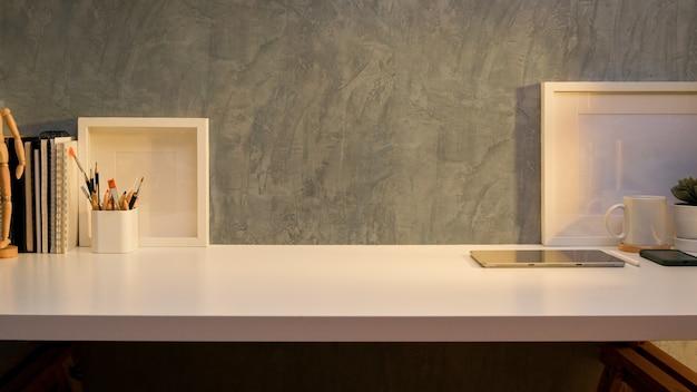 Vista ravvicinata della scrivania dell'home office con cancelleria, mock up frame, forniture e copia spazio