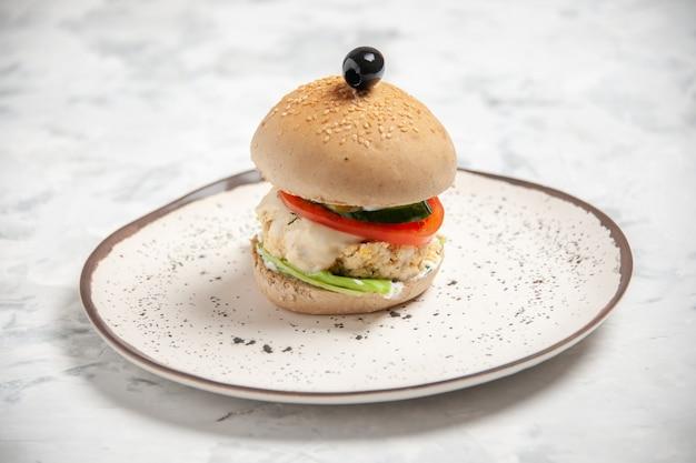 Vista ravvicinata di un delizioso panino fatto in casa su un piatto su una superficie bianca macchiata con spazio libero