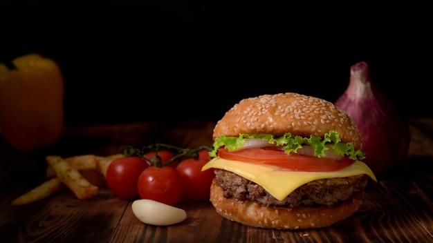 Chiuda sulla vista dell'hamburger di manzo saporito casalingo con gli ingredienti e le patate fritte