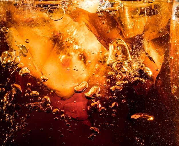 Vista ravvicinata dei cubetti di ghiaccio sullo sfondo scuro della cola