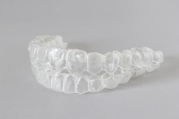 Primo piano vista di parentesi graffe invisibili o fermi invisibili su grigio, nuove apparecchiature ortodontiche