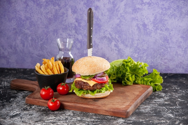 Vista ravvicinata del coltello in gustosa carne sandwich salsa ketchup patatine su tagliere di legno e pomodori con gambo sulla superficie di ghiaccio isolato