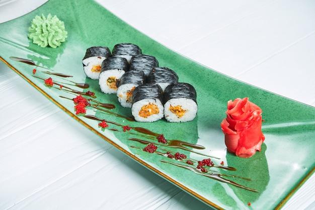 Chiuda sulla vista sul rotolo di sushi di maki con la cozza sul piatto verde isolato su fondo di legno bianco. cibo giapponese per sushi. frutti di mare