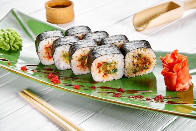Chiuda sulla vista sul rotolo di sushi di maki con il tonno sul piatto verde isolato su fondo di legno bianco. cibo giapponese per sushi. frutti di mare
