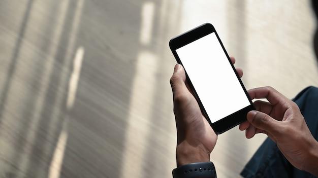 Vista ravvicinata delle mani dell'uomo che tengono lo smartphone con schermo bianco mentre si è seduti sul pavimento di legno.