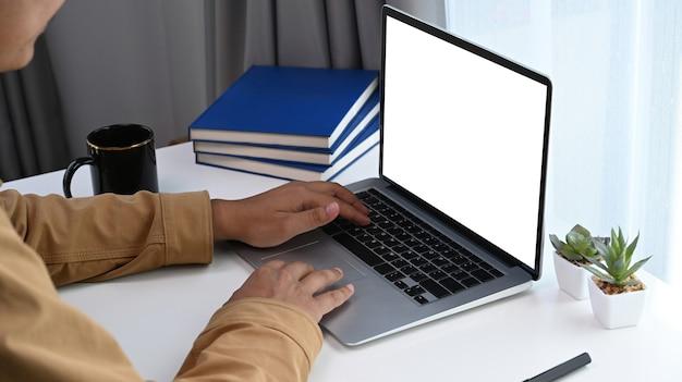 Vista ravvicinata dell'uomo che lavora al computer portatile in un comodo ufficio a casa.