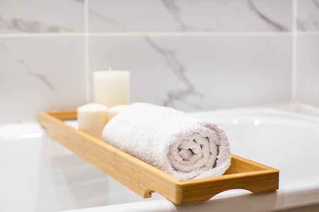 Vista ravvicinata di accessori da bagno in marmo bianco, asciugamani bianchi, candele e vista laterale dello spazio della copia