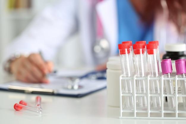 Vista ravvicinata di boccette mediche con medico, stagista o studente che lavora in laboratorio