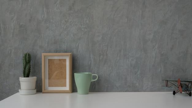 Chiuda sulla vista dell'area di lavoro moderna sulla tavola bianca con la parete grigia del sottotetto