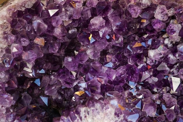 Chiuda sulla vista di una pietra di geode di cristallo ametista viola naturale.